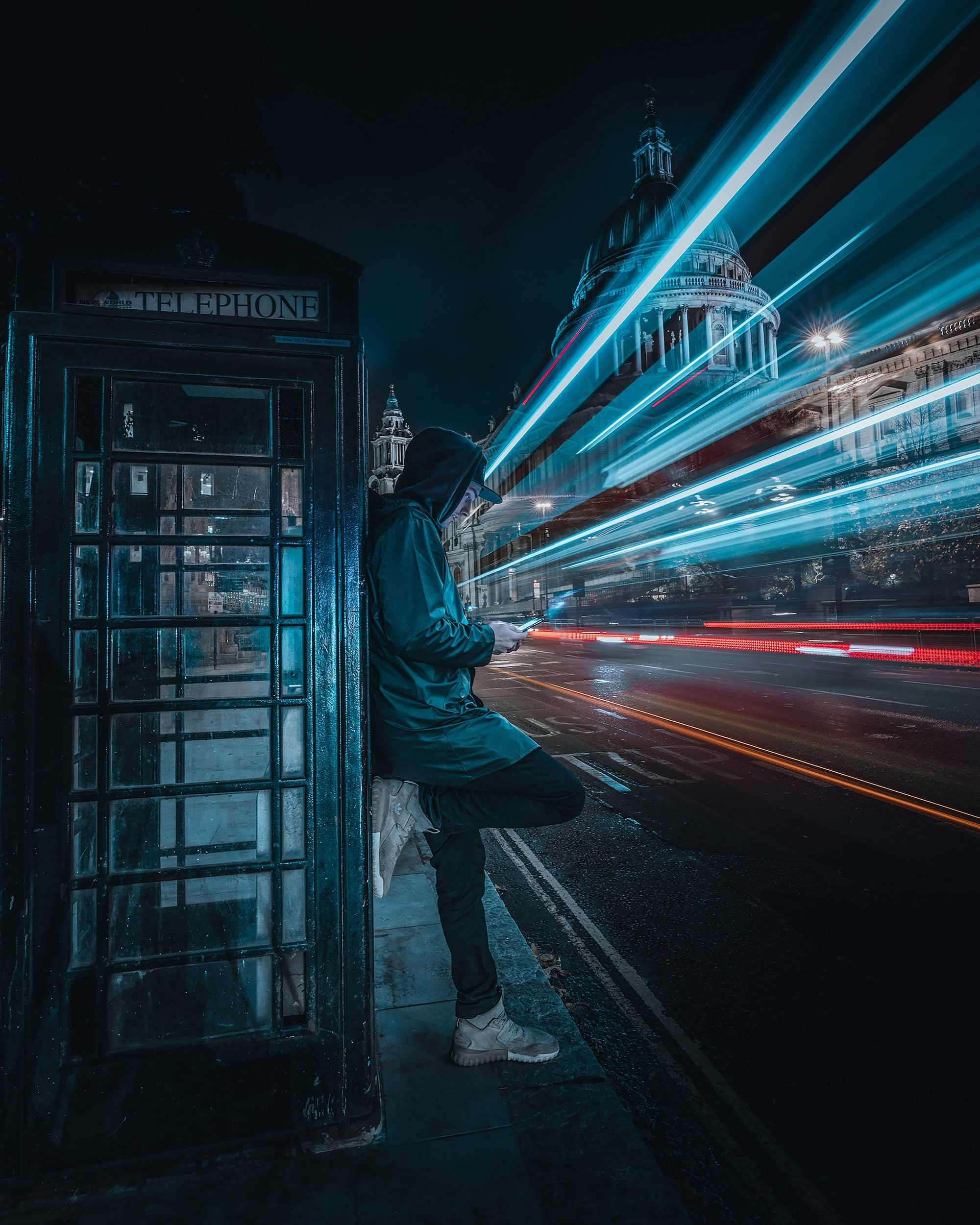 Lone man standing against telephone box with passing light trail