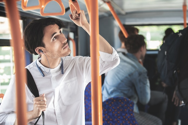 Person on a bus listening to an announcement using Ambient Sound mode