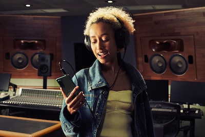 Woman listening to music on the Xperia 5 III with headphones in a music studio