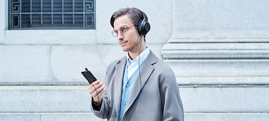 Man using Xperia 10 II with headphones to listen to music.