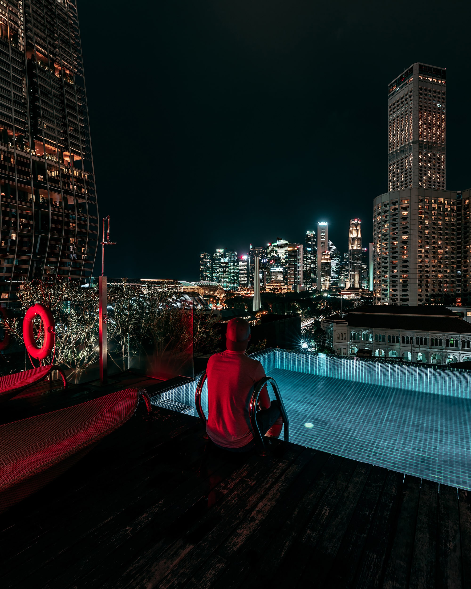 Hotel rooftop pool view of Singapore cityscape at night